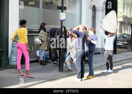 Film-Crew Fotografin fotografiert junge schwarze Mode-Modell in rosa Hose und gelben Top im Schnabel Street, Soho, - Stockfoto