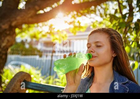 Junges Mädchen, sitzt auf der Bank, trinken Getränk aus der Flasche - Stockfoto
