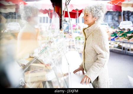 Reife weibliche Shopper kaufen Käse an den lokalen französischen Markt - Stockfoto