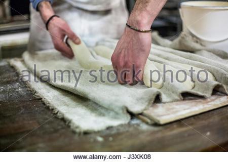 Bäcker arbeiten mit Teig in Bäckerei - Stockfoto