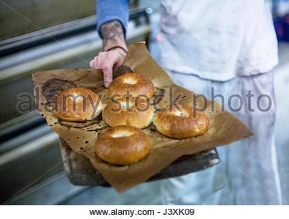 Baker mit frisch zubereitete bagels - Stockfoto