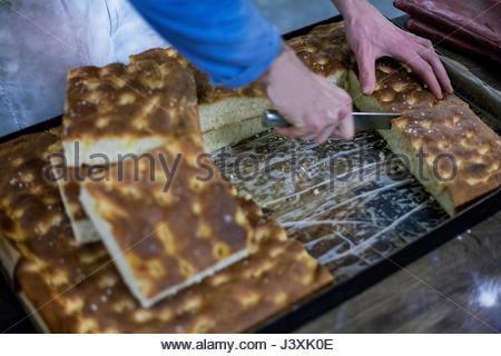 Baker schneiden frisch zubereiteten focaccia - Stockfoto