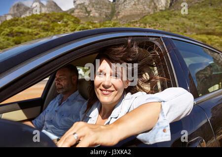 Paar in dem Auto auf Landstraße, Frau lehnte sich auf offene Fenster - Stockfoto