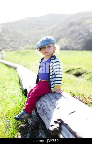 Porträt von männlichen Kleinkind in flache Mütze sitzt auf log - Stockfoto