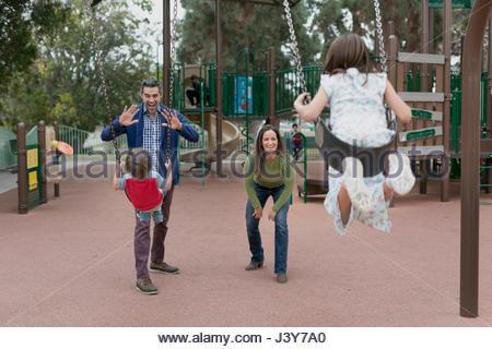 Familie beim Schaukeln im park - Stockfoto