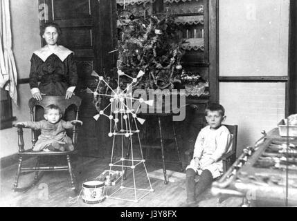 Eine Frau und [wahrscheinlich] ihre Söhne, mit einem kleinen Weihnachtsbaum mit Tisch, ca. -3. Sie posieren in der - Stockfoto