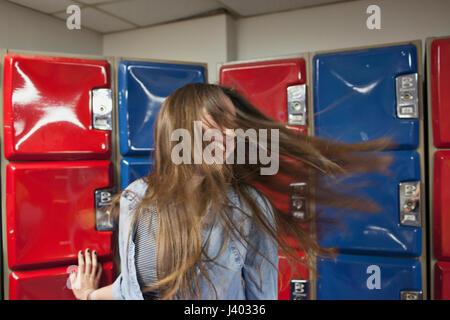 Eine junge Frau durch einige rote und blaue Spinde. - Stockfoto