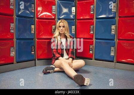 Eine junge Frau vor einige rote und blaue Spinde. - Stockfoto