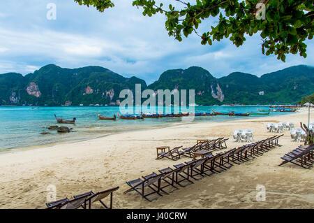 Blick auf Phi Phi Insel Strand Bucht gegen Longtail Boote vertäut und Küste - Stockfoto