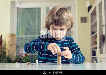 Kleiner Junge macht Stapel von Münzen, Geld am Tisch zu zählen. Finanzielle Verantwortung lernen und Planung Einsparungen - Stockfoto