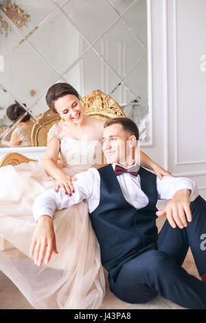 Braut im Kleid und der Bräutigam im schwarzen Anzug auf Sofa im Innenbereich in weisse Studio Interieur wie zu Hause - Stockfoto