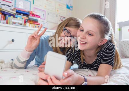 Zwei junge Mädchen posieren für Selfie im Schlafzimmer - Stockfoto