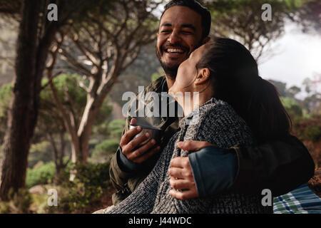 Glückliches junges Paar camping im Wald und Kaffeetrinken. Junger Mann und Frau zusammen im freien lächelnd. - Stockfoto