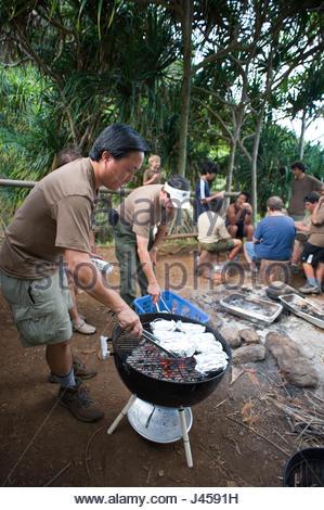 Erwachsenen Assistent Truppe Marktführer setzen Kartoffeln eingewickelt in Alufolie auf dem Grill zum Kochen, Kaaawa - Stockfoto