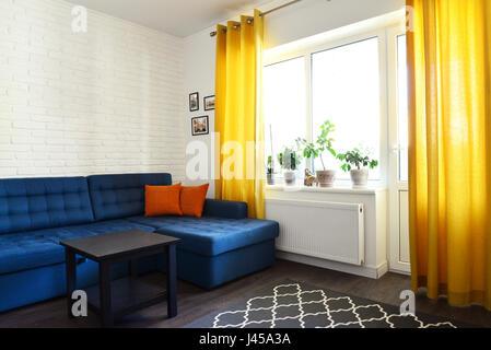 Saubere Familienzimmer Mit Blaue Couch, Weiße Ziegel Wand Und Gelbe Vorhänge.  Interior Design