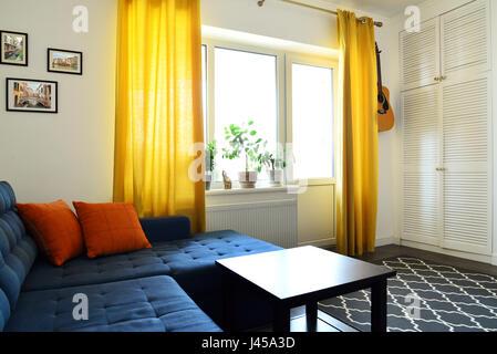 ... Wohnzimmer; Saubere Familienzimmer Mit Blaue Couch, Orange Marienburg  Und Gelbe Vorhänge. Interior Design Konzept