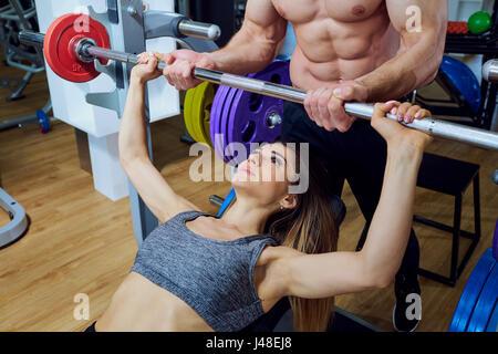 Mädchen machen Übungen mit einer Langhantel in der Sporthalle - Stockfoto