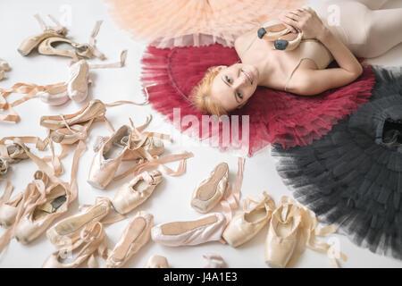 Lächelnd Ballerina liegt auf der bunten Tutus auf den weißen Boden - Stockfoto
