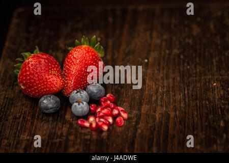frisch gepflückt Bauernhof Erdbeeren Blaue Beeren Closeup mit Granatapfelkernen mit Textfreiraum - Stockfoto
