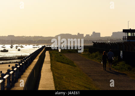 Paar hand in hand gehen in Richtung eine tiefstehende Sonne entlang eines Pfades der Ufermauer mit Southend Stadt - Stockfoto