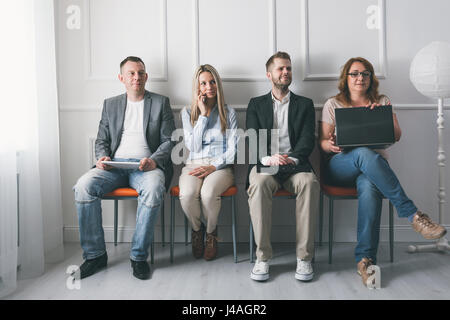 Gruppe von jungen kreativen Menschen sitzen auf Stühlen im Wartezimmer - Stockfoto