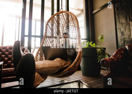 Männliche Führungskraft auf einer Weide Hängesessel im Büro Lounge und Blick auf Laptop sitzen. Mann zum Entspannen - Stockfoto