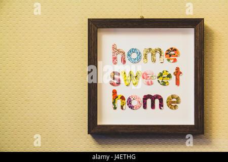 Umrahmt von Buchstaben traute Heim an einer Wand aufgehängt