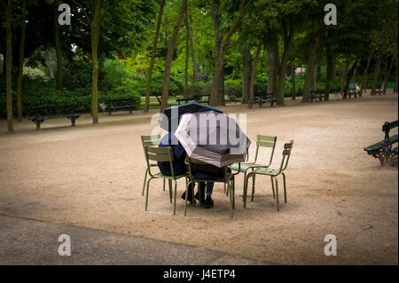 Junges Paar versteckt unter Sonnenschirmen im Jardin du Luxembourg - Stockfoto