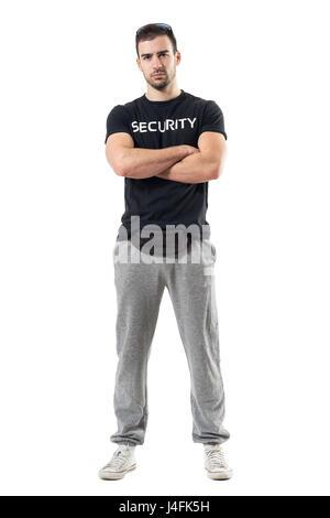 Harte macho Türsteher Gürteltasche mit verschränkten Armen Blick in die Kamera zu tragen. Ganzkörper-Länge-Porträt - Stockfoto