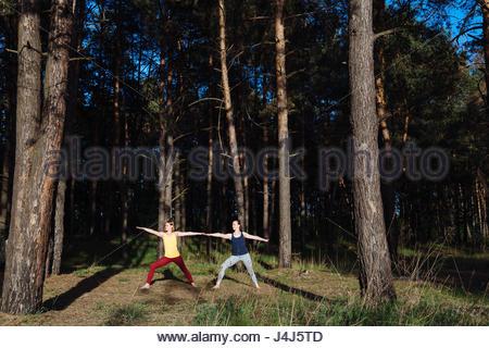 Zwei Mädchen Meditation Yoga Fitness Übung bei Sonnenuntergang im Wald. - Stockfoto