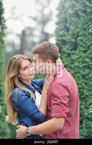 Junge schöne Mädchen starrte auf Kamera und wird von ihrem Freund geküsst. Liebe, Beziehung, Familie und Menschen - Stockfoto
