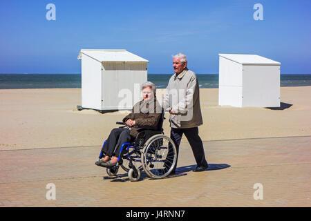 Pensionierter Mann unter deaktiviert ältere Frau im Rollstuhl für einen Spaziergang auf der Promenade entlang der - Stockfoto