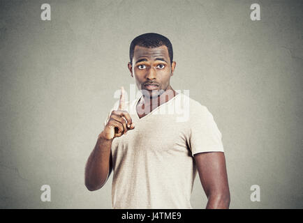 Closeup Portrait junger Mann nach oben mit der Idee, Lösung, mit dem Zeigefinger Nummer eins isolierte graue Wand - Stockfoto