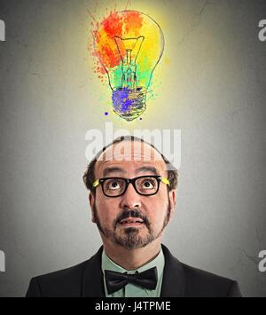 Kopfschuss Mann hat geniale Idee bunte Glühbirne über Kopf isoliert graue Wand Background. Menschliches Gesicht - Stockfoto