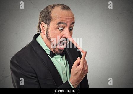 Mann mit langer Nase auf graue Wand Hintergrund isoliert. Lügner-Konzept. Menschlichen Gesichtsausdruck, Emotionen, - Stockfoto