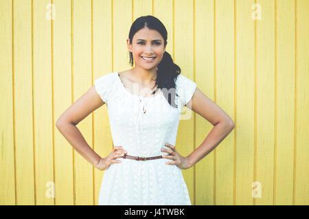 Closeup Portrait, glücklich zuversichtlich erfolgreiche hübsche junge Frau im weißen Kleid mit Händen auf den Hüften, - Stockfoto
