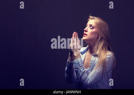 Junge Frau auf einem dunklen Hintergrund beten - Stockfoto
