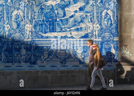 Portugal Fliesen Menschen, ein junges Paar Fuß vorbei an einer Wand des blauen Azulejos Kacheln auf der Seite der - Stockfoto