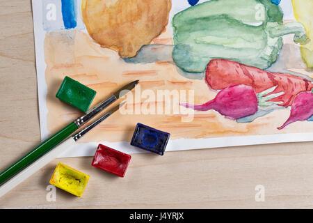 Stillleben mit Aquarellfarbe. Gemüse auf dem Küchentisch. Zwiebeln, Karotten, Paprika und Radieschen. Pinsel und - Stockfoto
