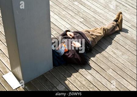 Mann schläft auf Boardwalk am Port Vell in Barcelona Spanien ES EU - Stockfoto