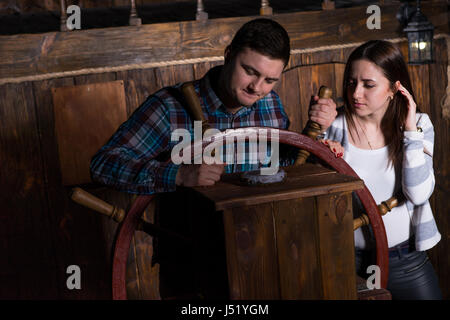 Junge Frau und Mann stehen an der Spitze des Schiffes und Blick auf den Kompass, das Spielkonzept Zimmer entkommen - Stockfoto