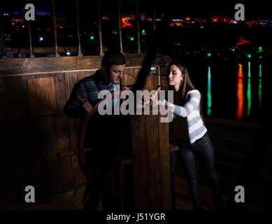 Junge Frau und Mann stehen an der Spitze des Schiffes und Blick auf den Kompass in der dunklen Nacht, das Spielkonzept - Stockfoto
