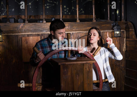 Junge Frau und Mann Stand an der Spitze des Schiffes und versucht, einen Ausweg zu finden mit Hilfe eines Kompasses - Stockfoto