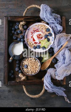 Smoothie Schüssel gesundes Frühstück. Erdbeer-Joghurt mit Müsli, Minze, Heidelbeeren, Krug mit Milch und Karambole - Stockfoto