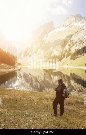 Rückseite des Wanderer mit Rucksack beobachten, die um den See und die Berge der Seealpsee, Schweiz - Stockfoto