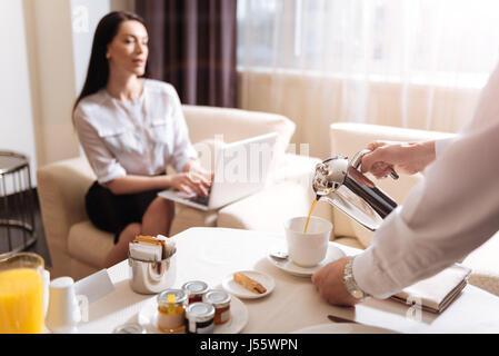Professionellen männlichen Kellner Kaffee in die Tasse Gießen - Stockfoto