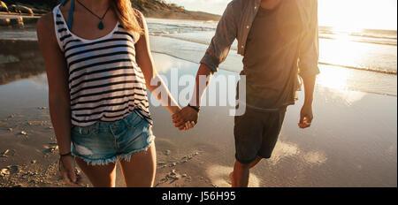 Schuss von junger Mann und Frau Hand in Hand und Wandern am Strand beschnitten. Paar am Strand spazieren. - Stockfoto