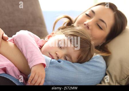 Nahaufnahme einer Mutter auf ihre kleine Tochter umarmt und schlafen zusammen liegend zu Hause auf Sofa mit warmem - Stockfoto
