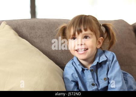 Porträt von ein glückliches Babymädchen auf der Suche oben auf einer Couch zu Hause - Stockfoto