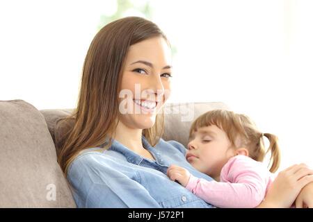 Mutter sah Sie mit ihrer Tochter über ihre Brust sitzt auf einer Couch zu Hause schlafen - Stockfoto
